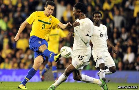 Brazil's Leandro Damiao (in yellow) and Ghana's Isaac Vorsah and Anthony Annan (far right)