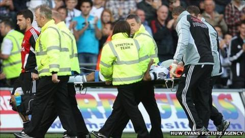 Neil Taylor is taken off on a stretcher