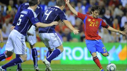 David Silva scores as several Scotland defenders try to block his shot