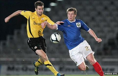 Glenavon defender Mark Turkington challenges Linfield forward Mark McAllister at Windsor Park