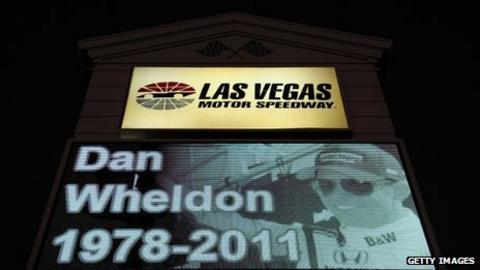 A memorial to Dan Wheldon is displayed on a Las Vegas Motor Speedway sign