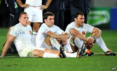 France players Imanol Harinordoquy, Dimitri Yachvili and Lionel Nallet sit dejectedly on the ground after their defeat
