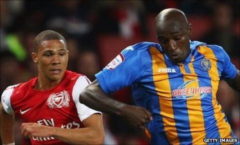Kieran Gibbs of Arsenal gives chase with Marvin Fof Shrewsbury Town