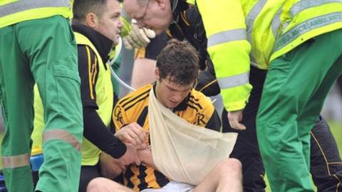 Paul Kernan is treated after disclocating a shoulder in the Casement Park game