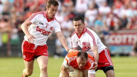 McGuigan and Jordan combine to halt the run of Armagh's Ciaran McKeever in this year's All-Ireland qualifier clash