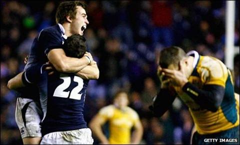 Australia's Matt Giteau holds his head in his hands after missing the decisive conversion, as Alex Grove and Nick de Luca celbrate victory for Scotland