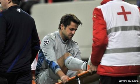 Lukasz Fabianski is stretchered off with a knee injury as Arsenal lose to Olympiakos