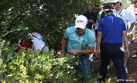 Luke Donald (right) helps Rory McIlroy search for his ball on the second hole