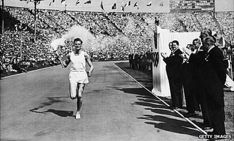 British athlete John Mark carries the Olympic torch into Wembley in 1948