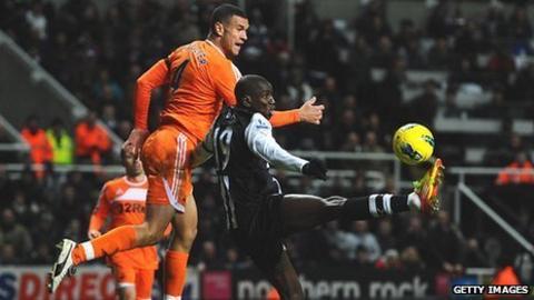 Swansea defender Steven Caulker challenges Newcastle striker Demba Ba