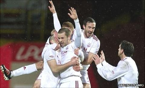 Aberdeen's Kari Arnason is mobbed after scoring the winning goal
