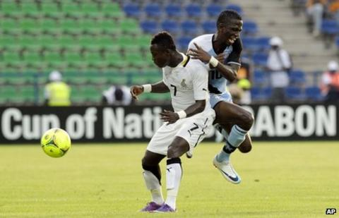 Botswana's Moemedi Moathlaping (R) is tackled by Ghana's Samuel Inkoom