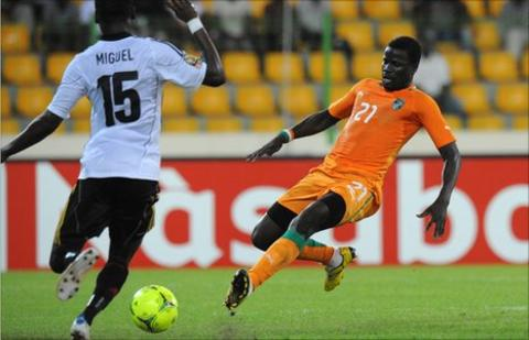 Angola's (in white) and Emmanuel Eboue of Ivory Coast (orange jersey)
