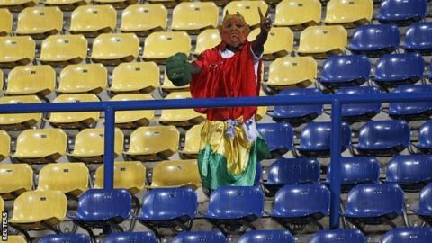 A Guinea fan stands among rows of empty seats