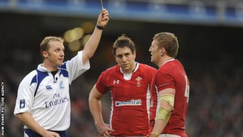 Wales back-row Ryan Jones looks on ruefully as referee Wayne Barnes sin-bins lock Bradley Davies