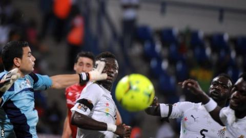 Tunisia goalkeeper Aymen Mathlouthi (L) challenges for the ball with Ghana players