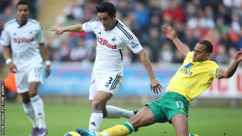 Swansea City's Neil Taylor is tackled by Norwich City's Elliott Bennett