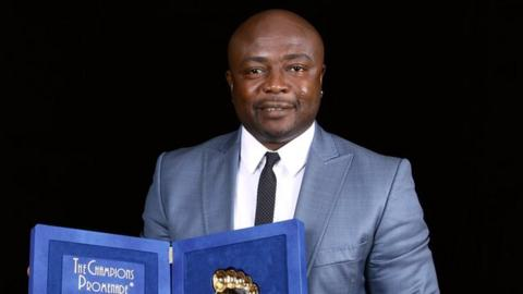 Abedi Pele holds an award he was given in 2011