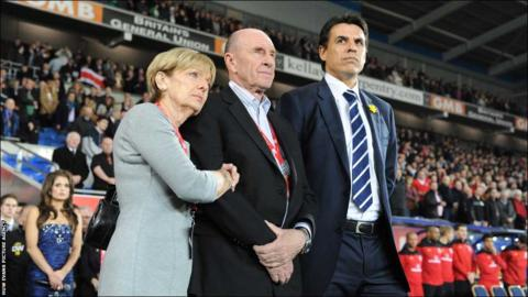 Wales manager Chris Coleman looks on during the national anthems with Gary Speed's parents Roger and Carol