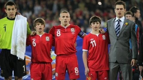 Wales' captain Craig Bellamy and Aaron Ramsey (right) stand alongside Gary Speed's sons Ed and Tommy before the game during the International Friendly at Cardiff City Stadium, Cardiff. Pic: David Davies/PA Wire
