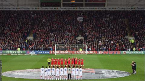 Both Wales and Costa Rica teams line up for the minute applause for the late Wales football manager Gary Speed at the Cardiff City Stadium