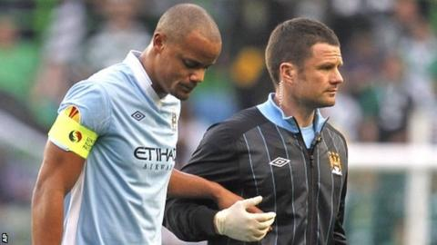 Kompany (left) is helped from the pitch after injuring himself in Portugal
