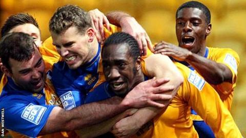Exodus Geohaghon is mobbed by jubilant Mansfield team-mates after his equaliser against Fleetwood