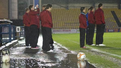 Players stand in the puddles at Almondvale before the postonement