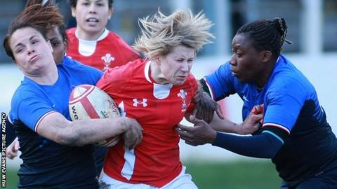 Mared Evans is tackled by France's Poublan Elode and Djossouvi Koumiba