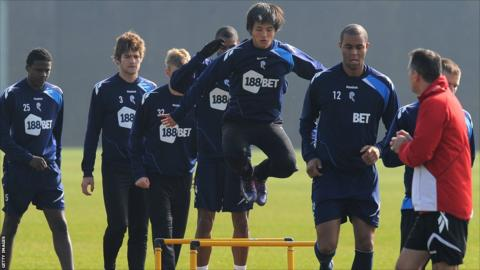Bolton Wanderers players jump a hurdle during a training session at their Euxton training ground near Bolton