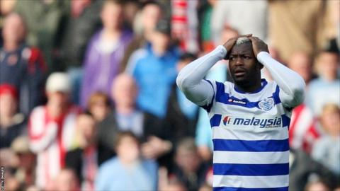 Queens Park Rangers' Djibril Cisse stands dejected after being given a red card