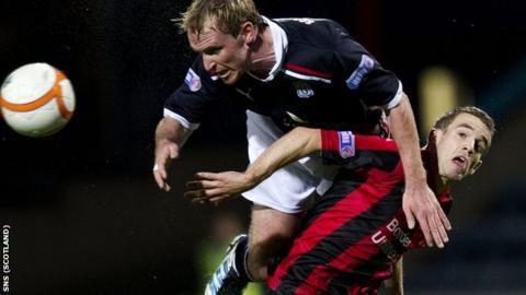 Dundee's Gary Irvine (left) rises above Craig Reid at Dens Park