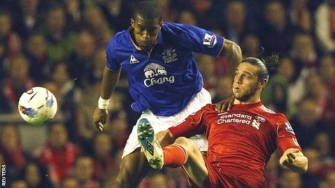Everton's Sylvain Distin (left) and Liverpool's Andy Carroll (right)