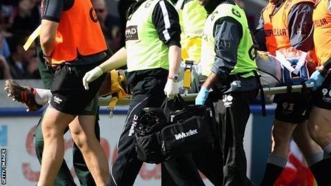 Tom Croft being stretchered off against Harlequins