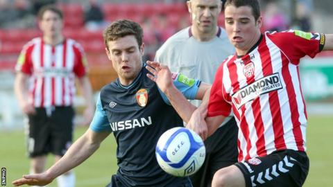 St Pat's John Russell battles with Stephen McLaughlin at the Brandywell