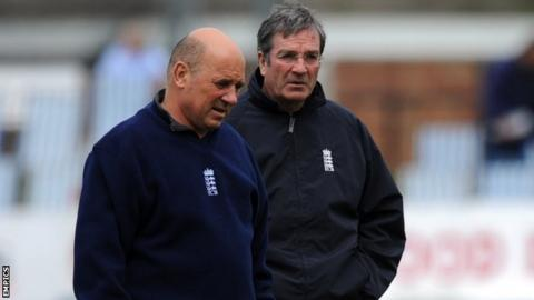 Umpires Mark Benson and Nick Cook carry out an inspection