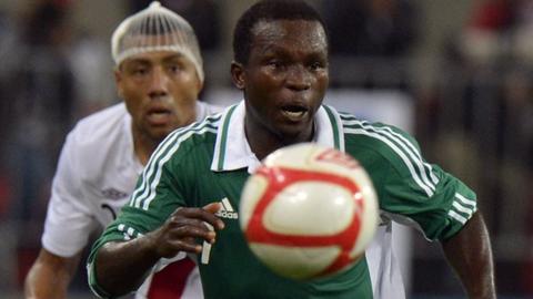 Nigeria's Ejike Uzoenyi is marshalled by Peru's Luis Ramirez
