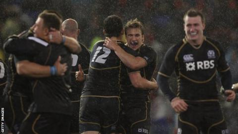 Scotland celebrate their 9-6 win over Australia in a wet and windy Newcastle