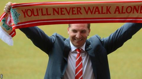 Brendan Rodgers holds a scarf aloft after being unveiled as Liverpool manager