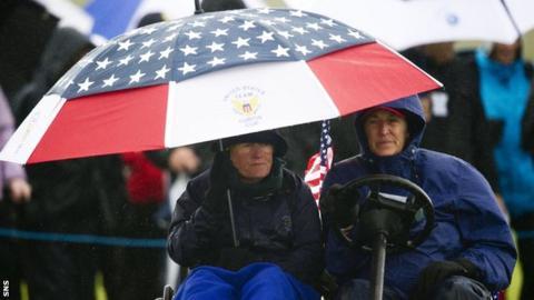 US skipper Pat Cornett (left) shelters under an umbrella as she nurses a broken ankle