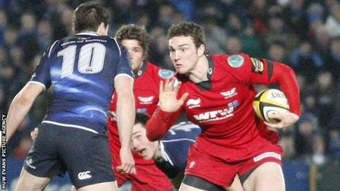Scarlets wing George North getting ready to hand off Leinster's Jonathan Sexton
