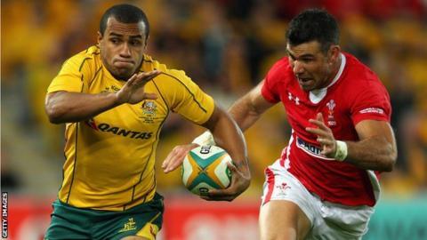 Australia scrum-half Will Genia runs away from opposite number Mike Phillips