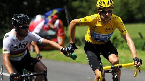 Mark Cavendish feeds Bradley Wiggins a water bottle