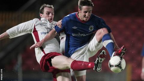 Greg Hall of Ards competes against Linfield's Michael Carvill