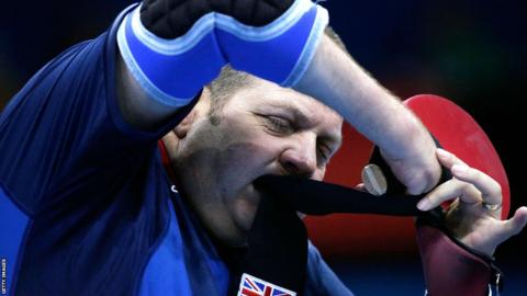 Paul Davies tightens the material on his racket during his Paralympic bronze medal win againt South Korea's Chang Ho Lee in the men's singles table tennis C1