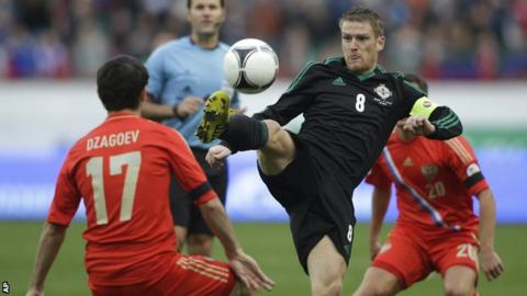 Northern Ireland's Steven Davis gets to the ball before Alan Dzagoev of Russia
