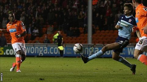 Nathan Delfouneso scores for Blackpool despite Jonathan Woodgate's attempt to block the shot