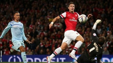 Olivier Giroud of Arsenal scores their first goal during the Capital One Cup third round match between Arsenal and Coventry City