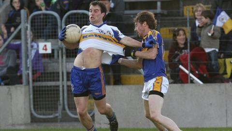 Ronan McRory of Errigal Ciaran is pulled back by Mullahoran opponent Norbert Smith