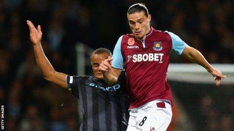Vincent Kompany challenges West Ham striker Andy Carroll